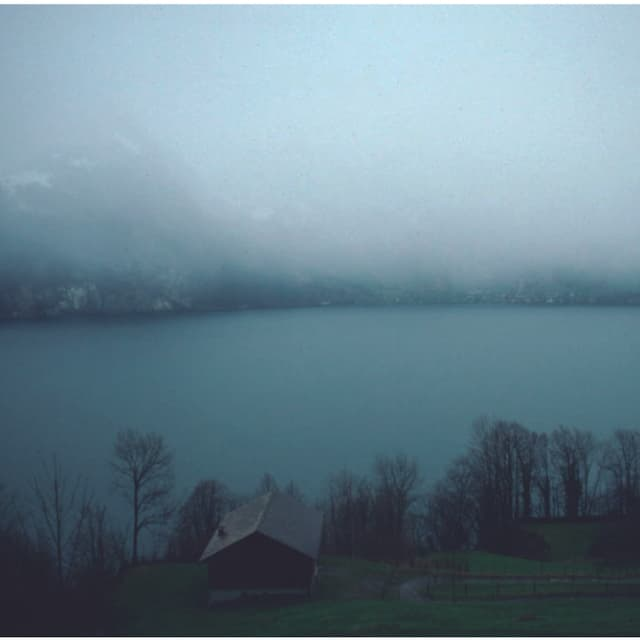 Eine mächtige Regenwolke hängt über einem See, das andere Ufer erkennt man nur noch knapp.