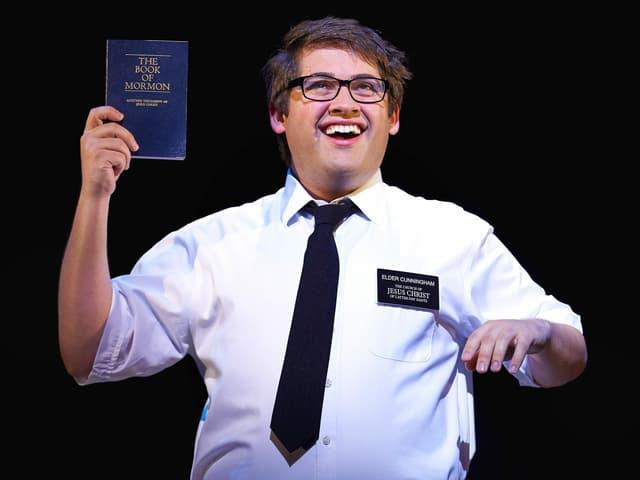 """Ein Bild aus dem Musical """"Book of Mormon"""". Ein Darsteller hält ein solches Buch hoch."""