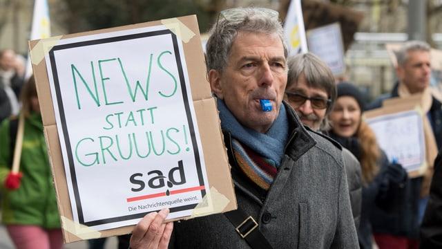 """Mann mit Trillerpfeife und Schild """"News ststt Gruus"""" und einem abgeänderten sda-Logo. Aus sda wird sad."""