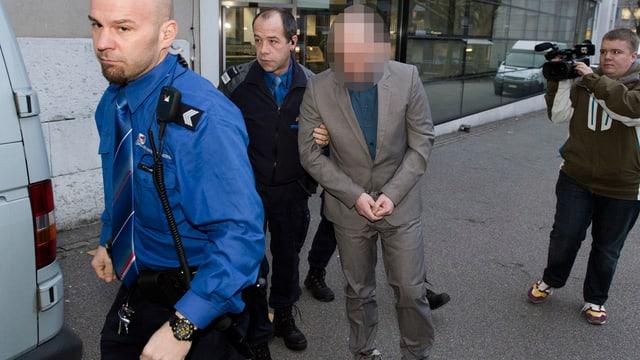 Polizisten führen einen Angeklagten zum Prozess, begleitet von einem Kameramann.