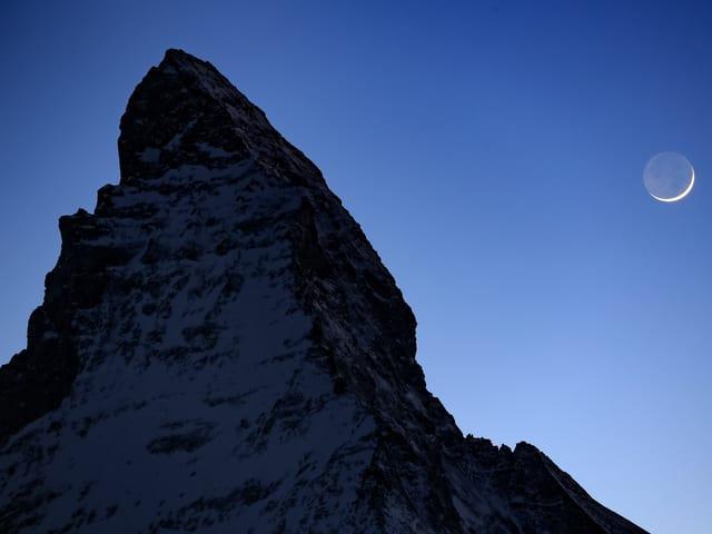 Das Mattherhorn der Nachthimmel leuchtet hell- bis dunkelblau, die Mondsichel ist zu erkennen.