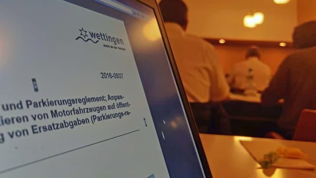 Computer-Bildschirm mit Einwohnerratsvorlage zu Parkierungsreglement, im Hintergrund Parlamentarier im Plenarsaal.