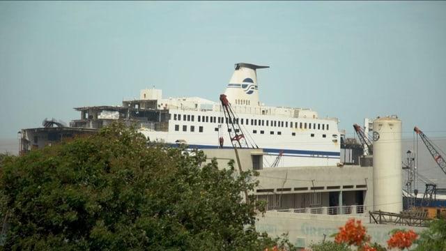 Weisses Kreuzfahrtschiff mit blauer Bemalung.