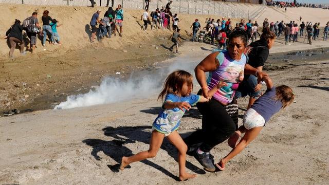 Eine Migrantin aus Honduras flüchtet mit ihren beiden Kindern vor der Tränengas-Wolke.