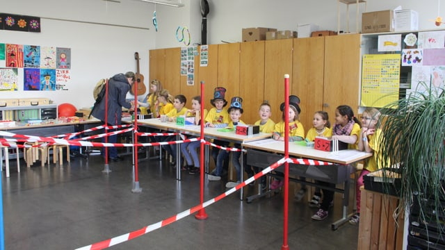 Schüler sitzen an einem langen Tisch. Absperrbänder davor.