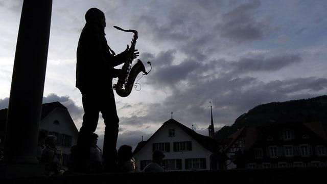 Saxophonist spielt im Abendlicht auf dem Dorfplatz Stans.