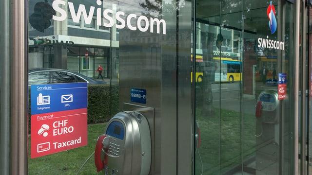 Swisscom-Schriftzug auf Glasscheibe einer Telefonzelle