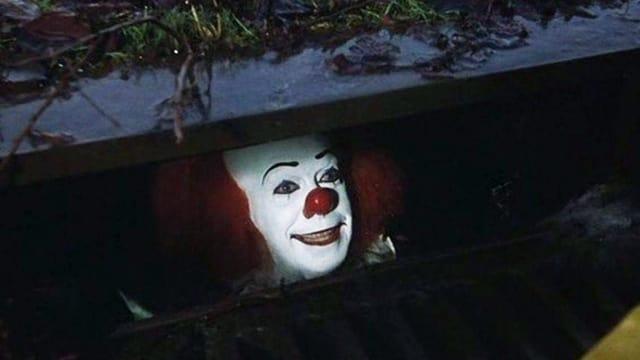 Clown schaut unter einem Bürgersteig hervor.