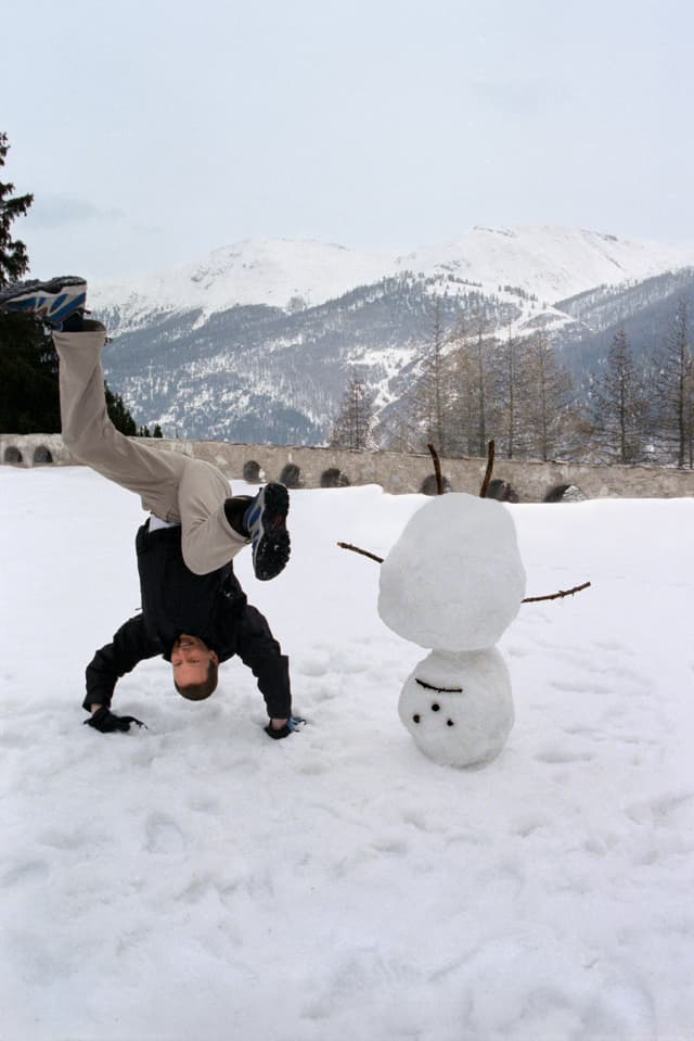 Der britische Künstler David Shrigley neben seinem Werk Upside down Snowman, am «Young Art Weekend 2000» vor dem Alpenschloss-Hotel Castell in Zuoz, Kanton Graubünden, 7. April 2000.