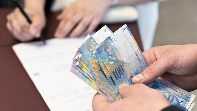 Eine Person unterschreibt ein Papier, während eine andere Person Geldnoten in den Händen hält.