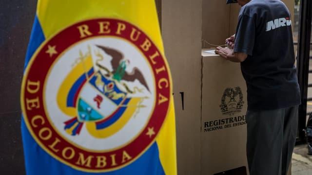 Purtret d'ina bandiera da la Columbia ed in um ch'emplaina il cedel da votaziun.