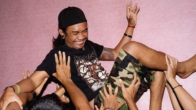 Eine Gruppe Menschen wirft einen lachenden Heavy-Metal-Sänger in die Luft.