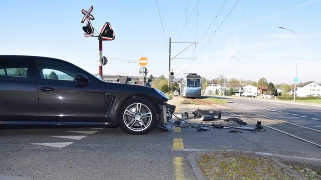 Porsche mit beschädigtem Frontbereich, Verschalung liegt am Boden, unweit der Bipperlisi-Gleise. Das Bähnli steht einige Meter weiter auf den Gleisen.