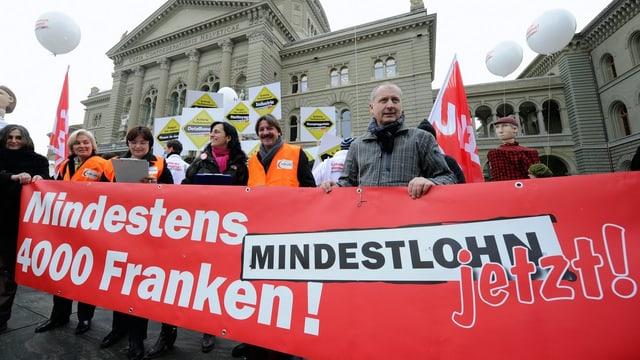 Demonstranten mit Banner vor dem Bundesplatz.