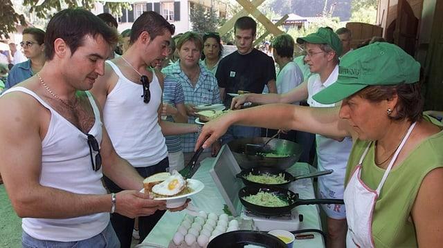 Köchinnen schöpfen jungen Männern Rösti und Spiegeleier.