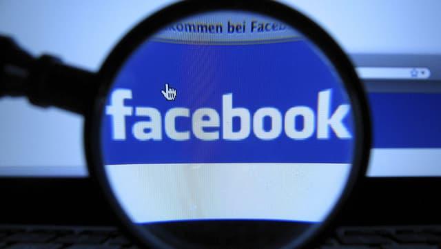 Facebook-Logo vergrössert durch eine Lupe