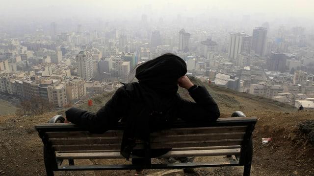 Frau mit Tschador sitzt auf Bank, im Hintergrund Teheran.