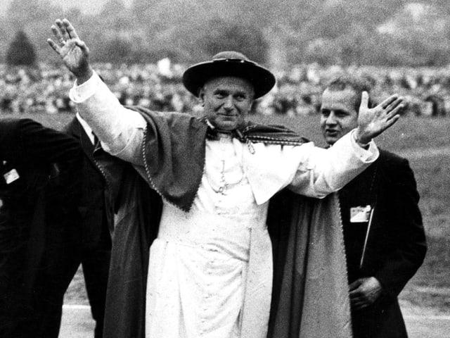 Der Papst mit weisser Soutane und Hut begrüsst die Menschen mit ausgestreckten Armen.