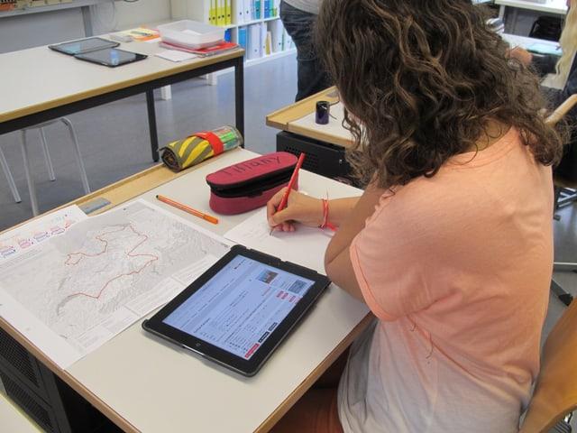 Schülerin an Pult mit iPad und Schweizer Karte