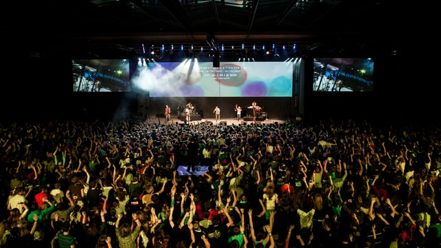 Eine Band steht auf der Bühne vor begeisterten Jugendlichen.