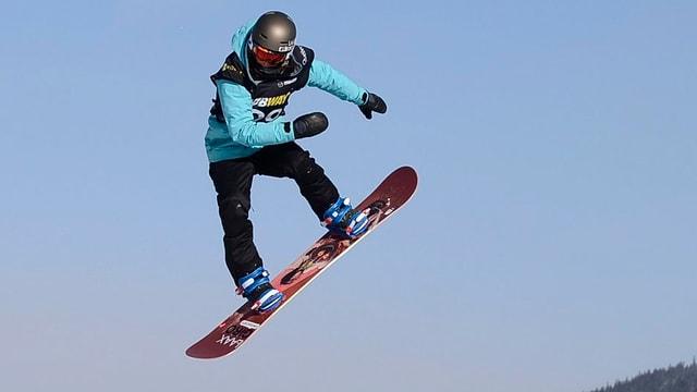 Sina Candrian auf dem Sowboard in der Luft vor blauem Himmel