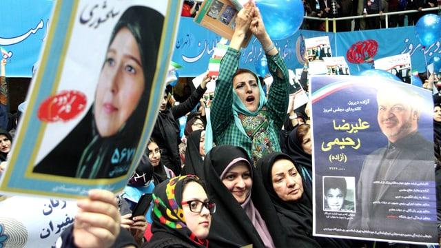 Frauen mit Wahlplakaten, offenbar an einer Wahlkampfveranstaltung.