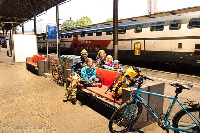 Familie wartet mit Velos am Bahnhof vor einem Zug