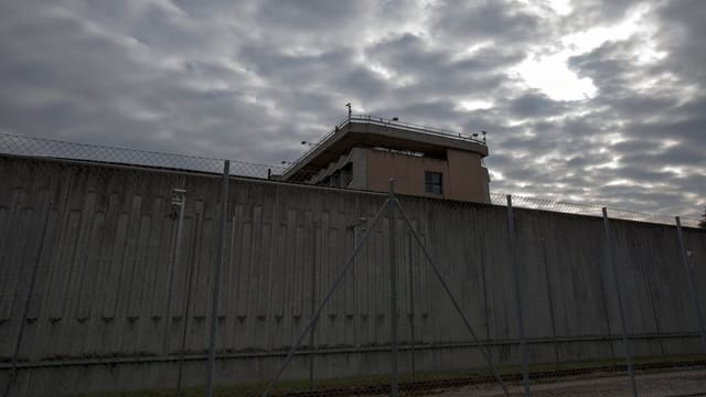 Eine Aufnahme einer hohen, grauen Mauer eines Gefängnisses.