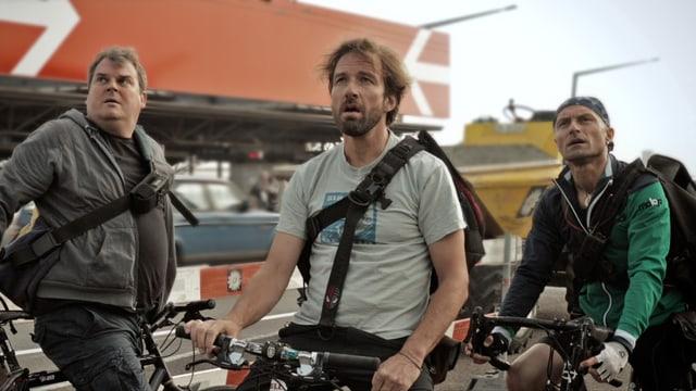 Drei Männer mit Fahrrädern schauen erstaunt ins Leere (Ausschnitt aus dem Film).