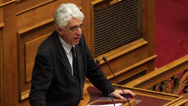 Il minister tar in pled al pult en il parlament.