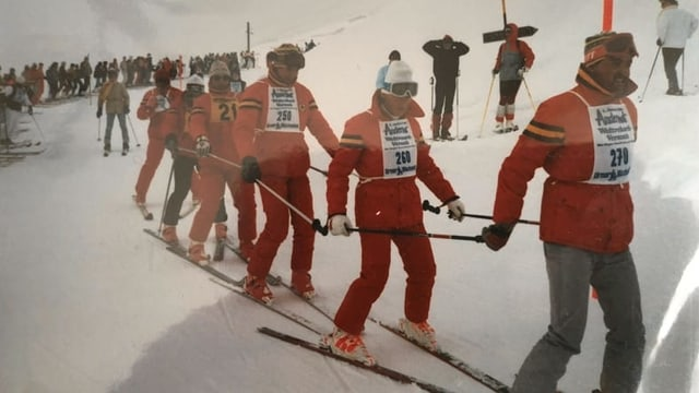 Menschen auf Skiern in roten Anzügen.