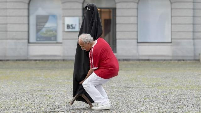 Mann mit Puppe, die eine Burka trägt.