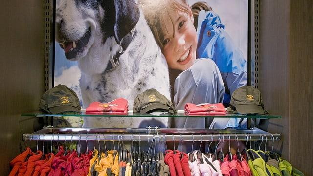 Plakat, Mädchen, das sich an einen Hund lehnt. Im Vordergrund sind Kleider in einer Sportxx-Filiale sichtbar.