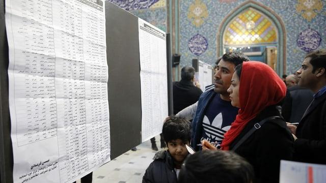 Menschen in einem Wahllokal studieren Listen.