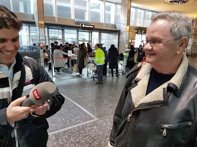 Ein Mann mit Mikrofon und ein lachender Mann mit Brille und Lederjacke.