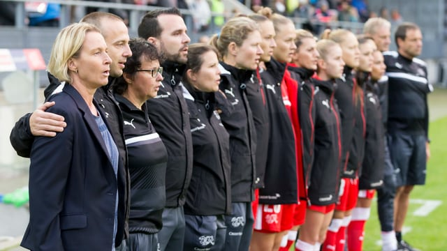 Das Team umarmt sich beim Abspielen der Nationalhymne.