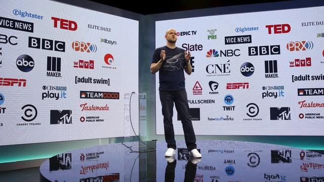 Junger Mann steht auf einer Bühne; im Hintergrund zahlreiche Logos von bekannten internationalne Medienunternehmen (BBC, TED, NBC etc.)