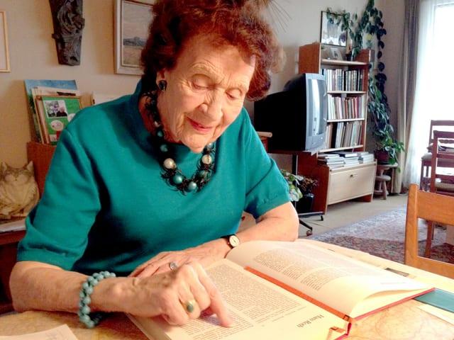 Elisabeth Pfluger beugt sich über ein Buch und liest aus einer Geschichte über Hans Roth.