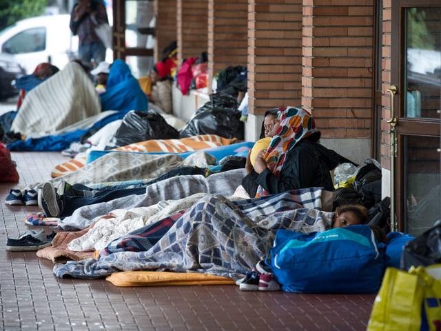 Menschen in Schlafsäcken am Bahnhof Como