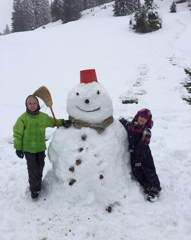 Ein Schneemann mit einer Grösse von über einem Meter. Er trägt einen roten Deckel als Hut und Tannzapfen als Knöpfe.