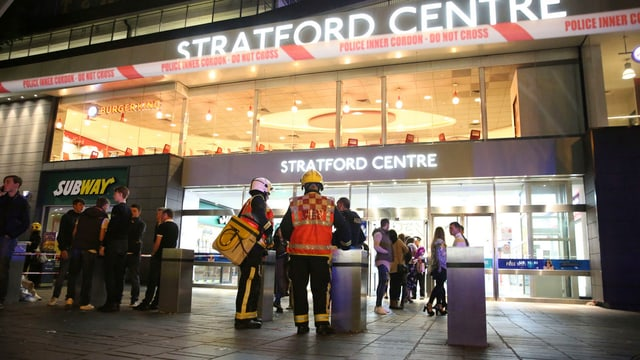 Rettungskräfte stehen vor einem Einkaufszentrum.