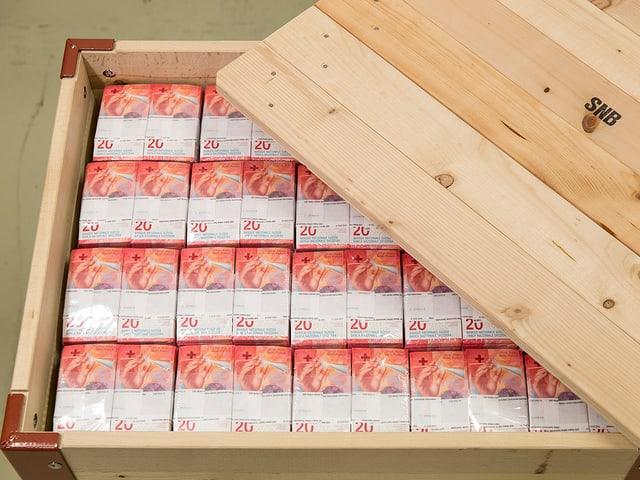 Halboffene Kiste mit Bündel neuer 20er-Noten