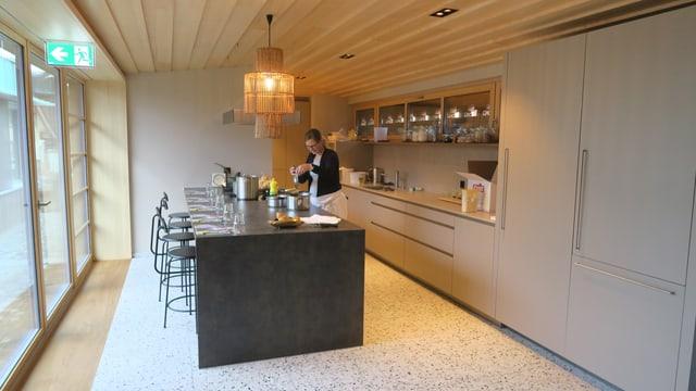 Eine Frau bereitet Essen zu in einer Wohnküche.