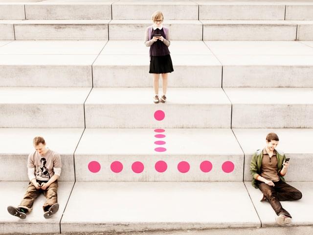 Zwei Männer sitzen auf einer Treppe, etwas weiter oben steht eine Frau. Alle schauen auf ihr Smartphone. Sie sind durch eine gepunktete Linie verbunden.