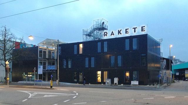 Dreistöckiges, dunkles Gebäude mit versetzten Fenstern. Auf dem Dach der Schriftzug Rakete.