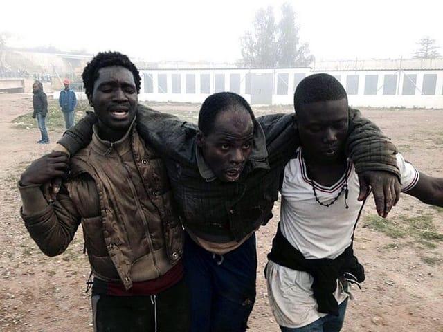 Zwei Afrikaner tragen einen erschöpften Kollegen