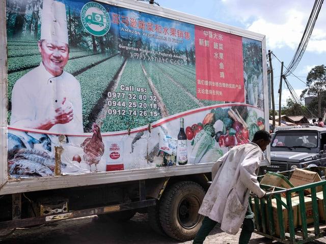 Ein Afrikaner schiebt seinen Handwagen vor einer chinesischen Werbung vorbei.