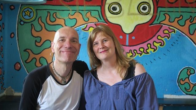 Ein Mann und eine Frau vor einer bunten Wand
