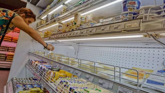 Eine Frau greift in ein Kühlregal mit Milchprodukten.