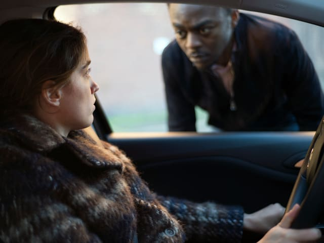 Eine Frau sitzt am Steuer eines Wagens, durch dessen Fenster ein Schwarzer sie anschaut.